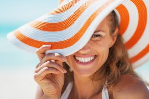 Woman in sun hat smiles after visiting her Grafton cosmetic dentist